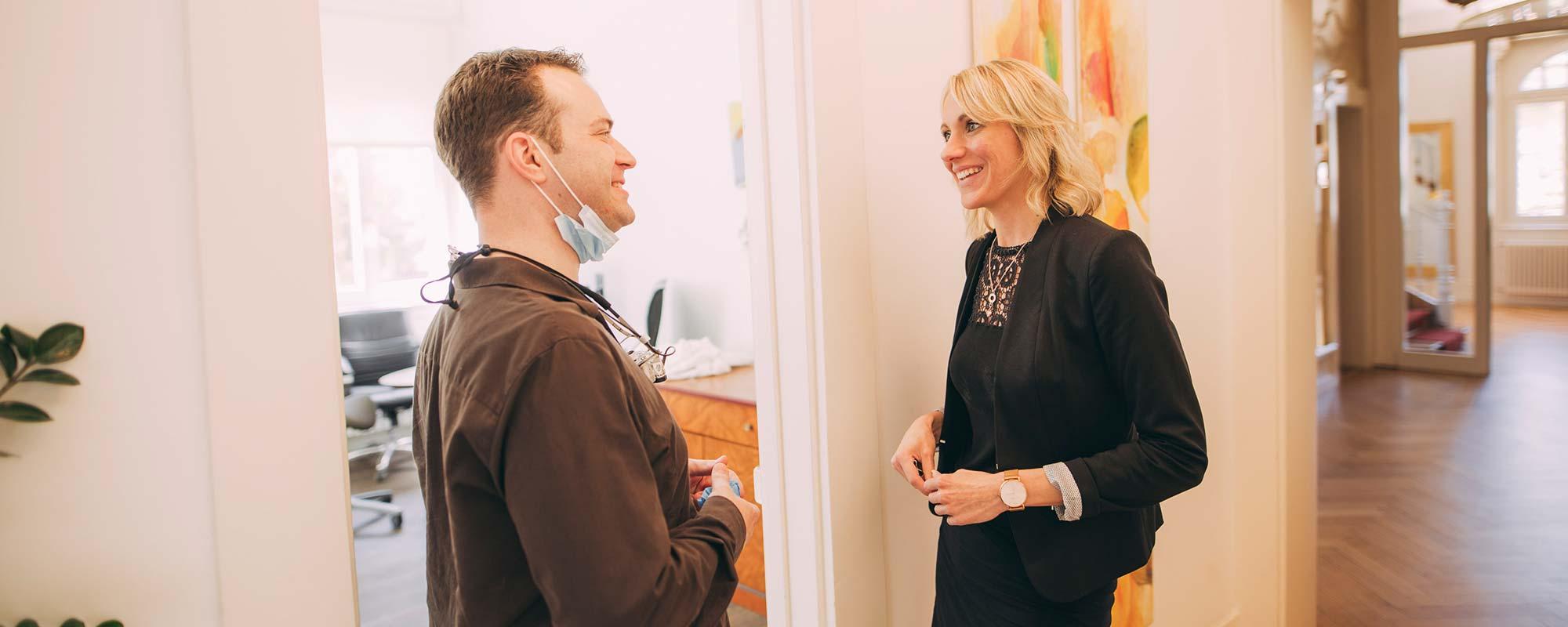 Zahnarzt Dr. Andreas Euchner und Mitarbeiterin unterhalten sich auf dem Flur der Privatpraxis Villa Seldeneck in Baden-Baden.