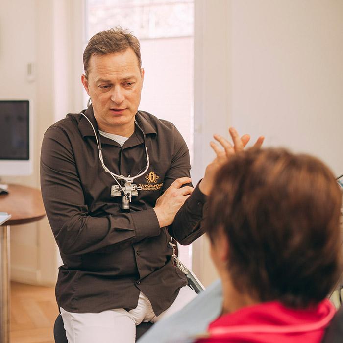 Dr. Torsten Kamm berät Patientin, ob Weisheitszähne ziehen in Baden-Baden Sinn macht oder nicht.