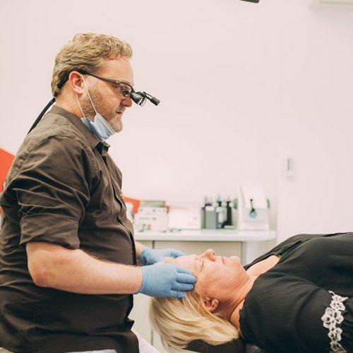 Zahnarzt Dr. Karsten Kamm überprüft Fehlfunktion des Kiefergelenks vor der CMD-Therapie in Baden-Baden.