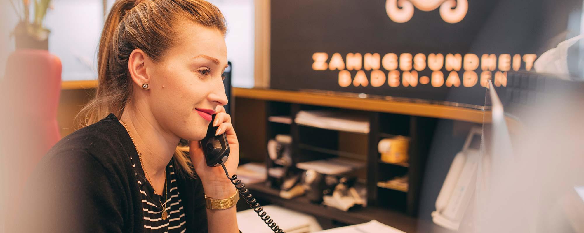 Mitarbeiterin beim Zahnarzt in Baden-Baden geht freundlich ans Telefon.
