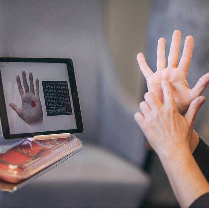Mitarbeiterin beim Zahnarzt in Baden-Baden zeigt mit der Handfläche die Größe einer Zahnfleischentzündung.
