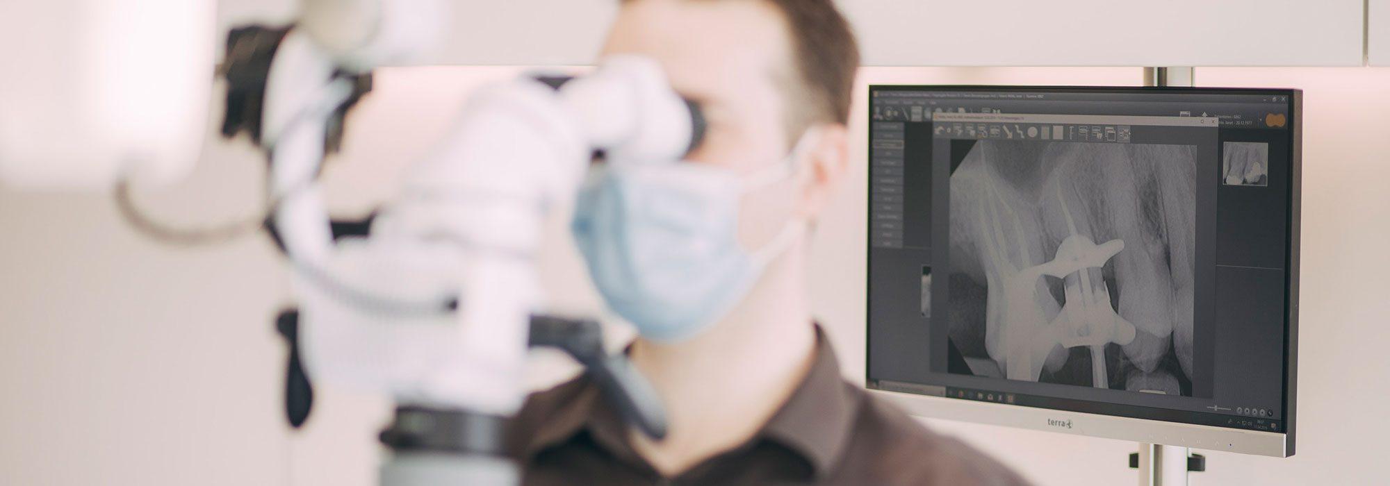 Dr. Andreas Euchner schaut durch Dentalmikroskop, im Hintergrund Vergrößerung der Zahnwurzelbehandlung in Baden-Baden.