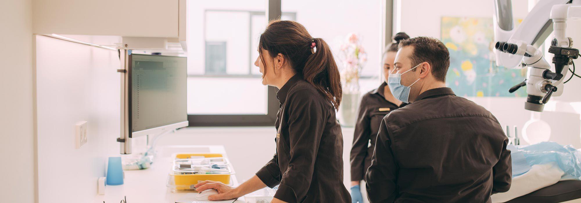 Dr. Susann Kamm und Dr. Andreas Euchner schauen sich Details zur Zahnwurzelbehandlung in Baden-Baden auf dem Monitor an.