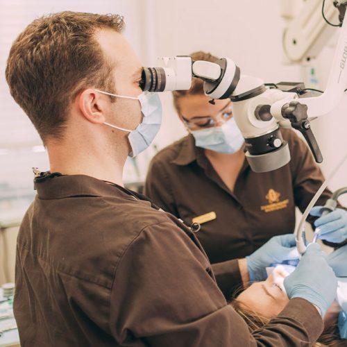 Dr. Andreas Euchner schaut durch Dentalmikroskop bei Wurzelbehandlung in Baden-Baden.