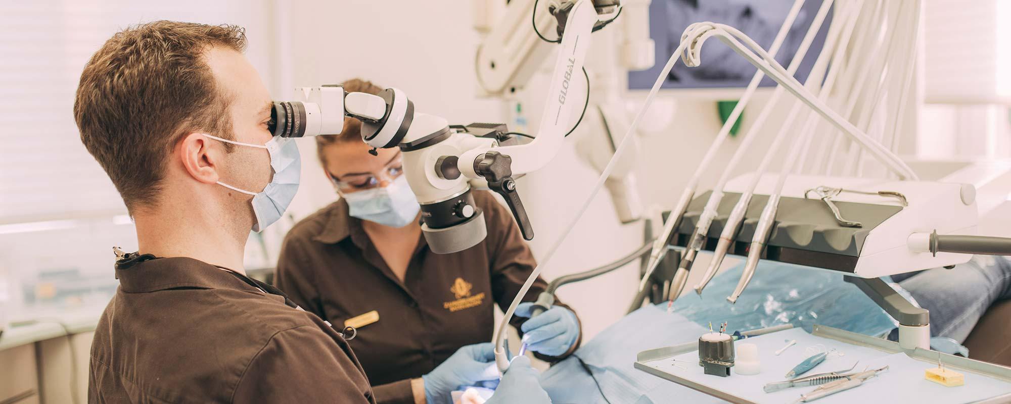Dr. Andreas Euchner schaut bei der Zahnwurzelbehandlung in Baden-Baden durch ein Dentalmikroskop.