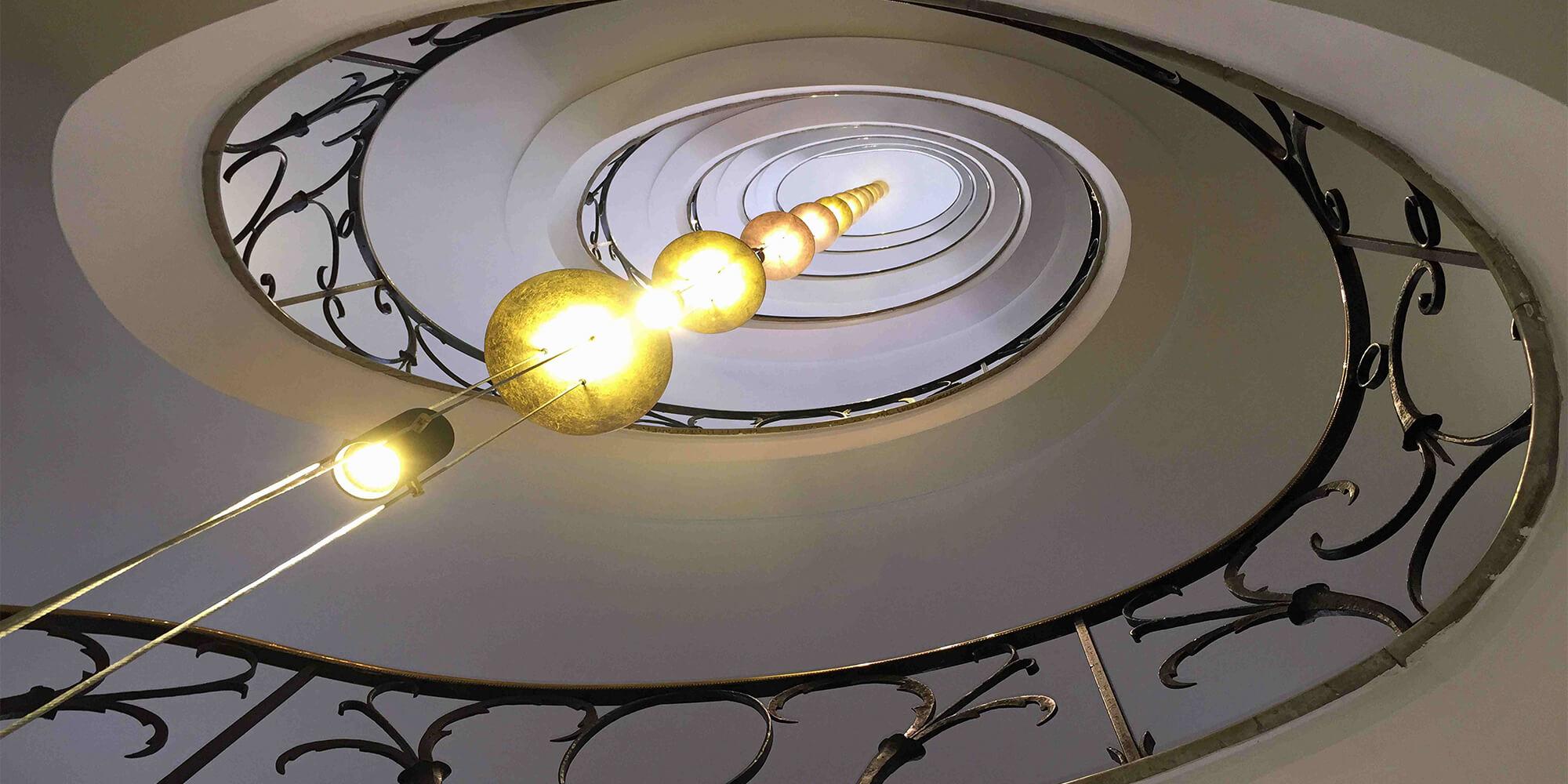 Eindrucksvolle Lampen schmücken Treppenhausarchitektur, die in der Zahnarztpraxis ZBB in Baden-Baden ausgestellt wird.