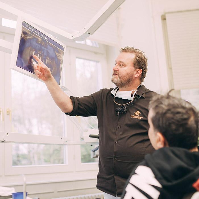 Dr. Karsten Kamm zeigt Patienten Möglichkeiten mit Zahnimplantaten in Baden-Baden.