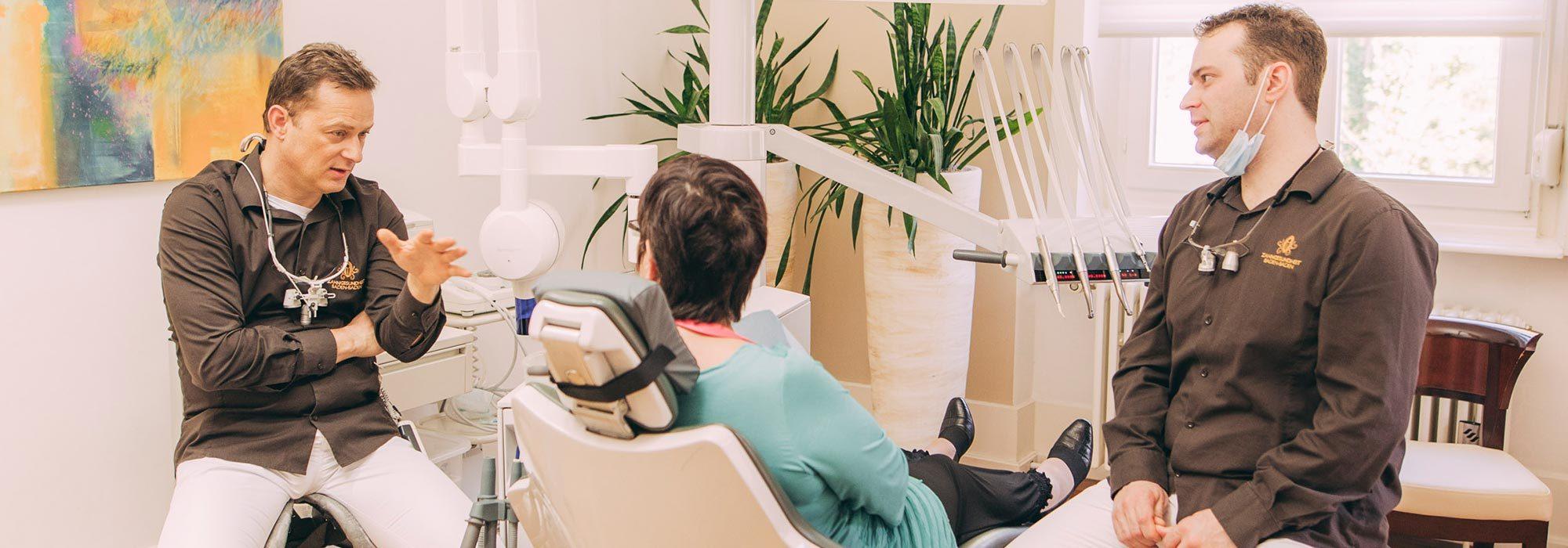 Zahnärzte Dr. Torsten Kamm und Dr. Andreas Euchner beraten eine Patienten zur Zahnwurzelbehandlung in Baden-Baden.