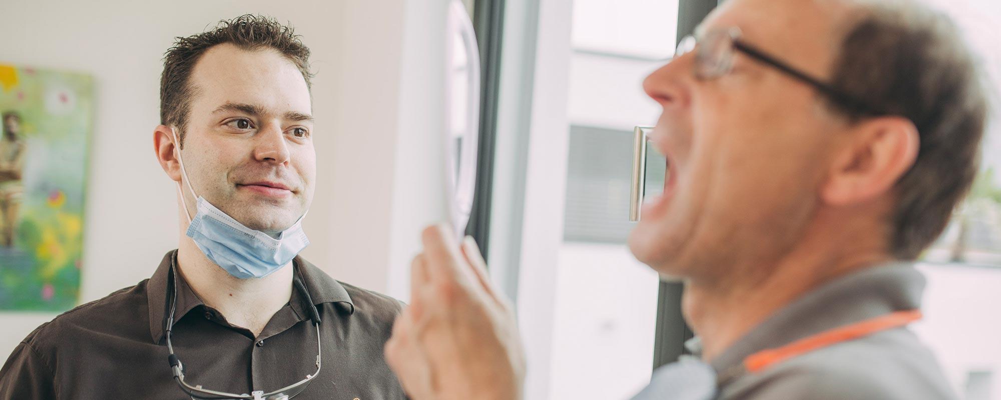 Dr. Andreas Euchner hat mit Zahnumformung in Baden-Baden Patienten geholfen, der im Spiegel das Ergebnis betrachtet.