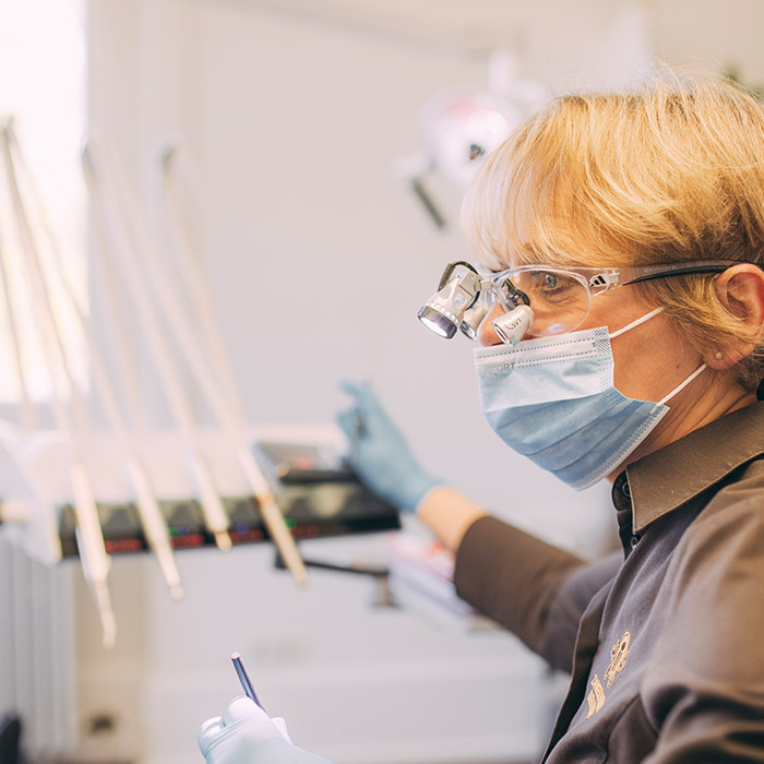 Dentalhygienikerin mit Lupenbrille bereitet die Prophylaxe Behandlung in Baden-Baden vor.