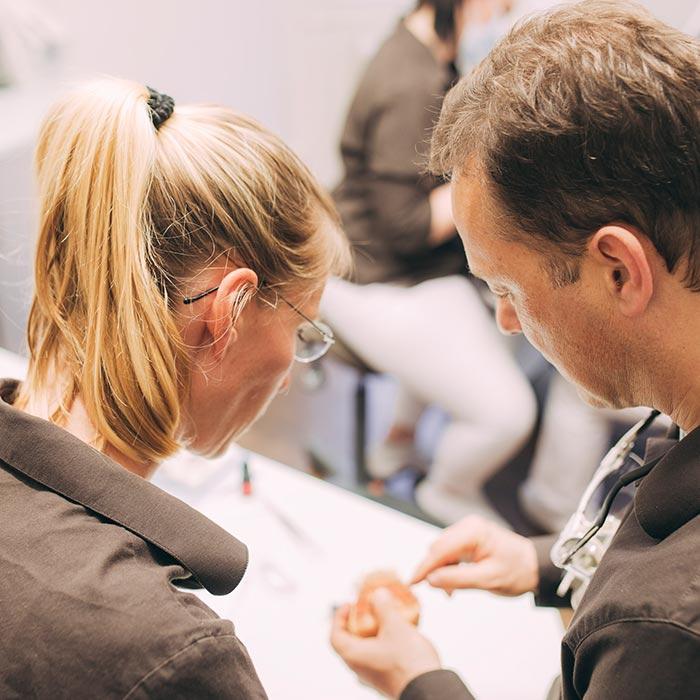 Dr. Torsten Kamm und Zahntechnikerin passen gemeinsam Zahnersatz für Patienten in Baden-Baden an.