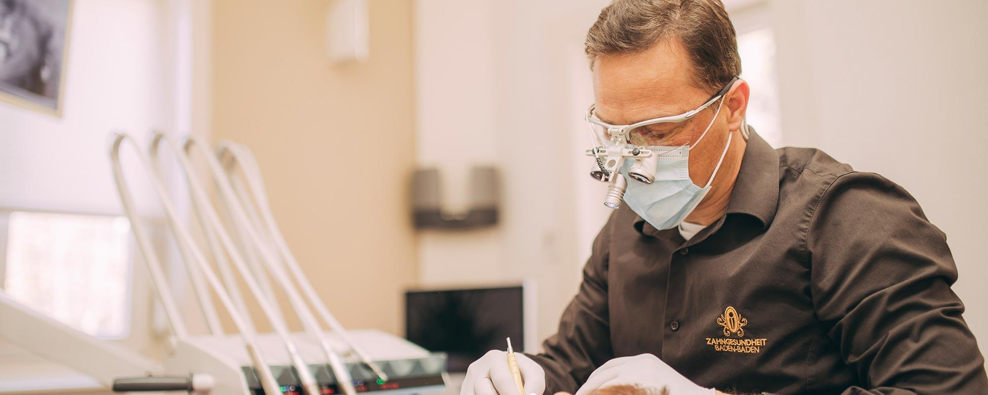 Dr. Torsten Kamm arbeitet mit Lupenbrille bei der Parodontosebehandlung in Baden-Baden.
