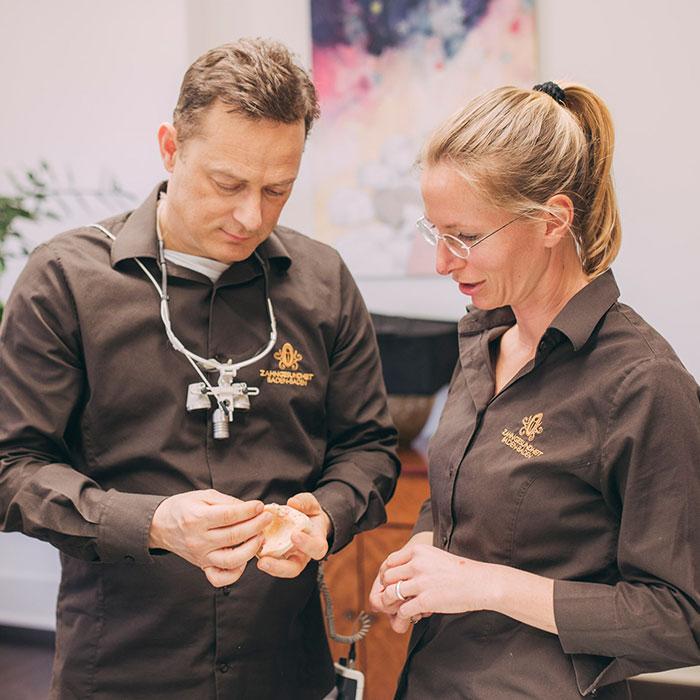 Zahnarzt Dr. Torsten Kamm unterhält sich mit Mitarbeiterin über Möglichkeiten für feste Zähne an einem Tag in Baden-Baden